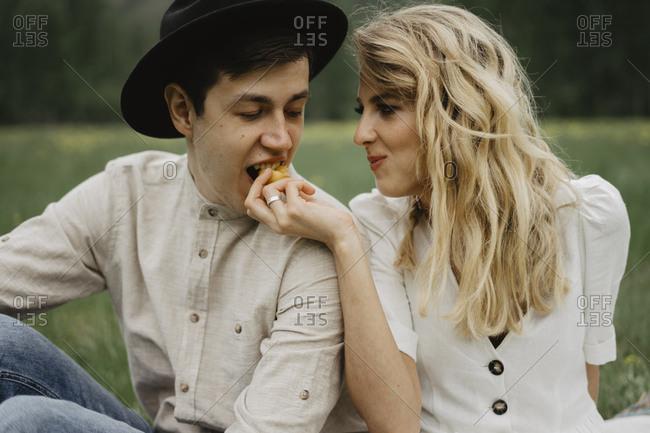 Woman feeding man a piece of fruit