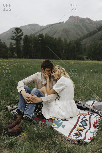Couple embraced on blanket in field