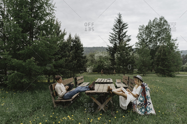 Man playing small guitar for woman while she rests on a bench