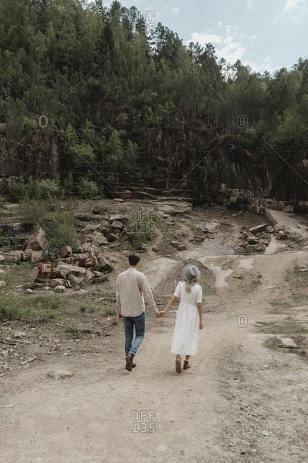 Rear view, of couple walking towards a forest