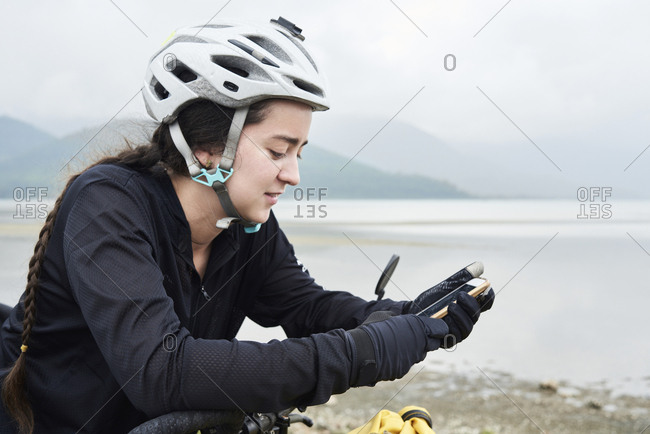 Cyclist backpacker using technology while stopped in road wearing helmet and braids