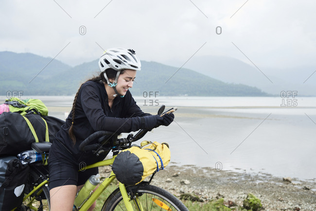 Cyclist backpacker using smartphone chatting smiling while stopped in road wearing helmet and braids