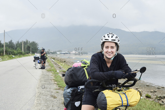 Cyclist backpacker female looking at camera smiling while stopped in road wearing helmet and holding smartphone