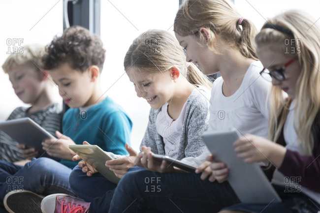 Smiling pupils with tablets on school corridor