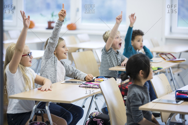 Happy pupils raising their hands in class
