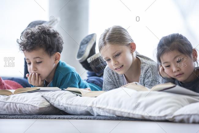 Pupils lying on the floor reading books in school break room