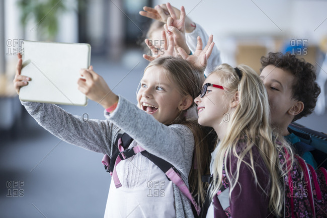 Happy pupils taking a selfie with tablet in school