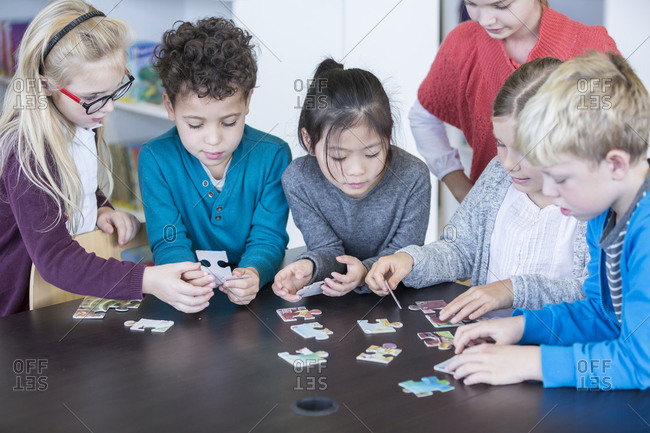 Pupils playing jigsaw puzzle in school together