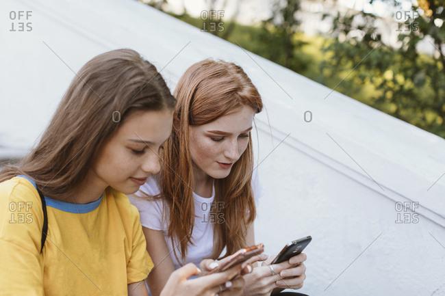 Teens sitting on steps texting, Minsk, Belarus