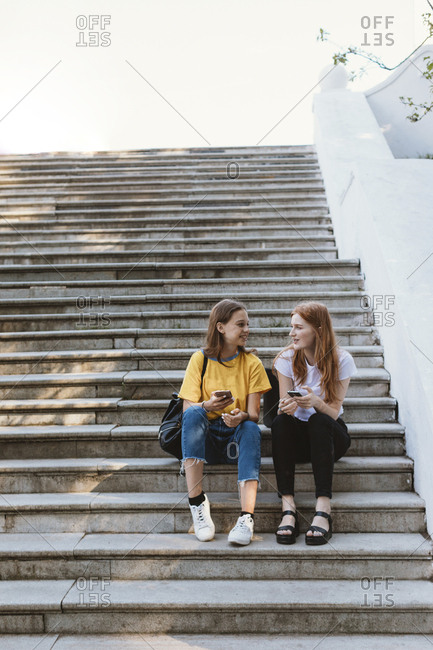 Two teenagers sitting on steps texting, Minsk, Belarus