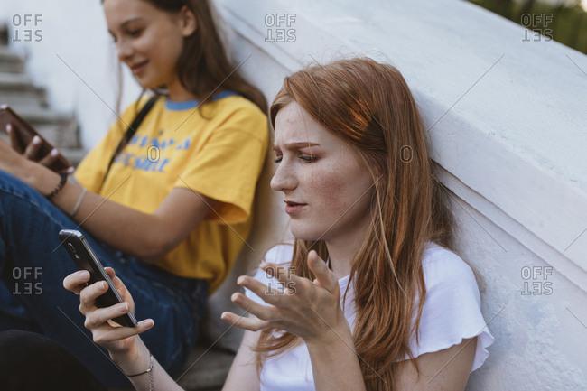 Teens sitting on steps using cell phones Minsk, Belarus