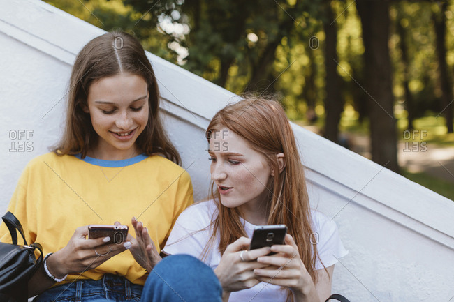 Two teenagers sitting at park texting, Minsk, Belarus