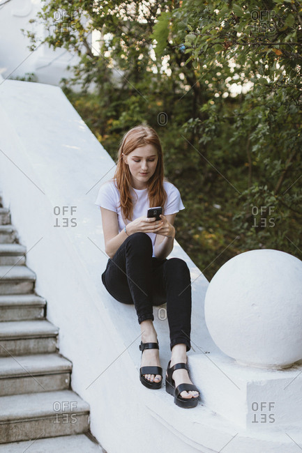 Teen with red hair sitting on railing using cell phone, Minsk, Belarus