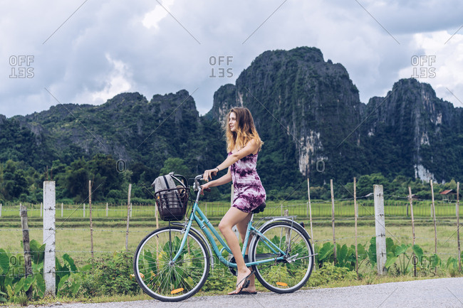 Pretty woman on bicycle on rural road
