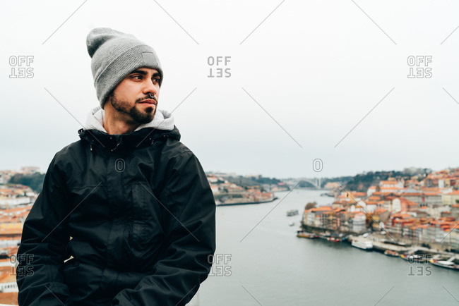 Handsome young man standing on background on old European city with orange roofs