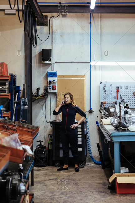 Woman talking on the phone in a mechanical garage