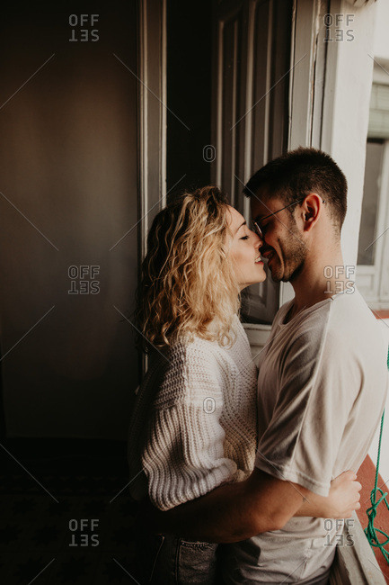 Side view of couple embracing and bonding at home
