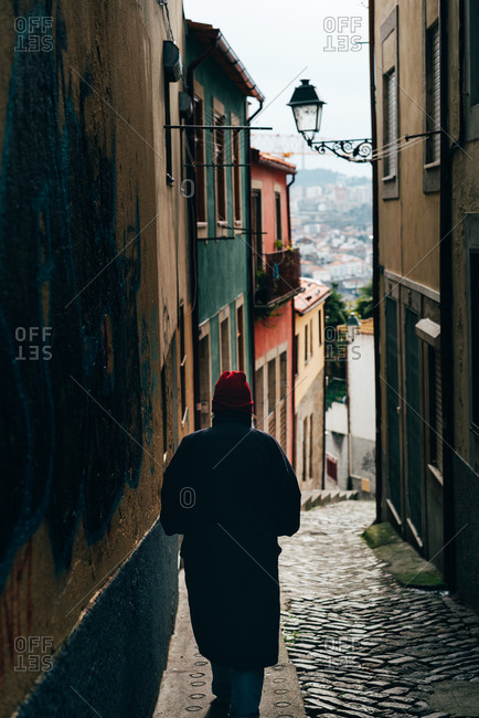 Back view of man in red hat walking down the narrow street in old town