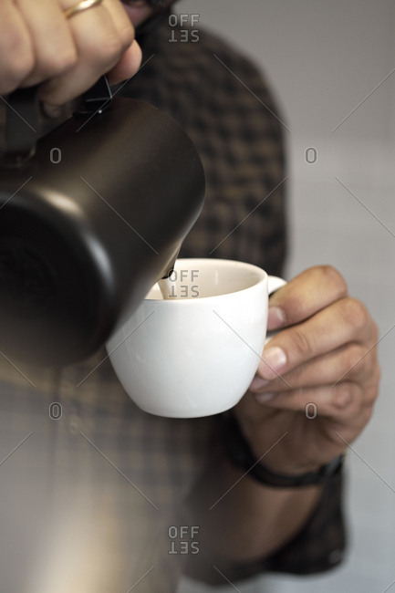Crop hands of barista pouring whipped cream from pitcher to the ceramic mug