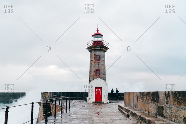 Unrecognizable tourists standing at beacon tower at wavy ocean