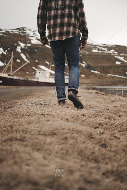 Back view of crop tourist man walking on dry grass at roadside in Iceland