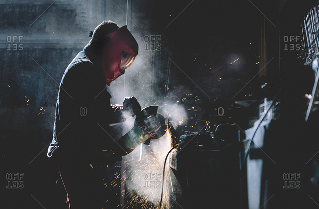 Man works with grinder cutting metal