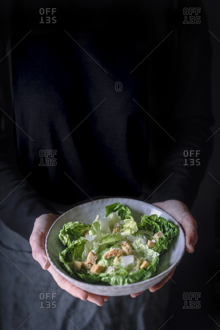 Crop mature woman in dark clothes holding bowl with tasty salad