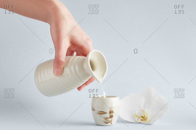 Crop view of hand holding white ceramic pitcher and pouring water into cup with floral ornament standing on white background with elegant white orchid nearby