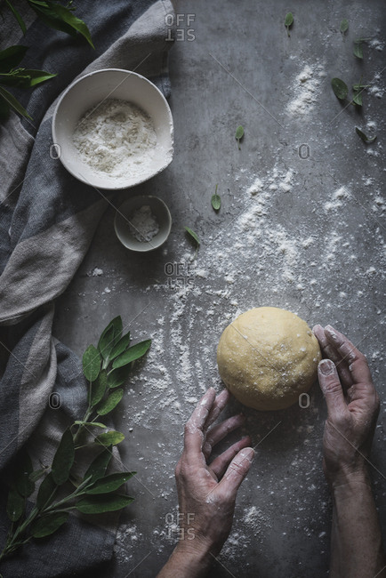 Crop shot from above of senior person kneading ball of soft dough on marble counter sprinkled with flour