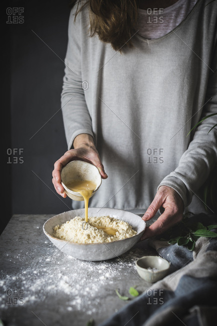 Faceless shot of woman making dough and pouring beaten egg into bowl with flour while making dough