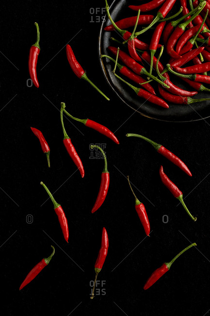 Top view of red hot peppers and bowl on black background