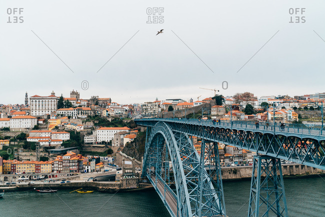 Bridge over the river and old European town with orange roofs