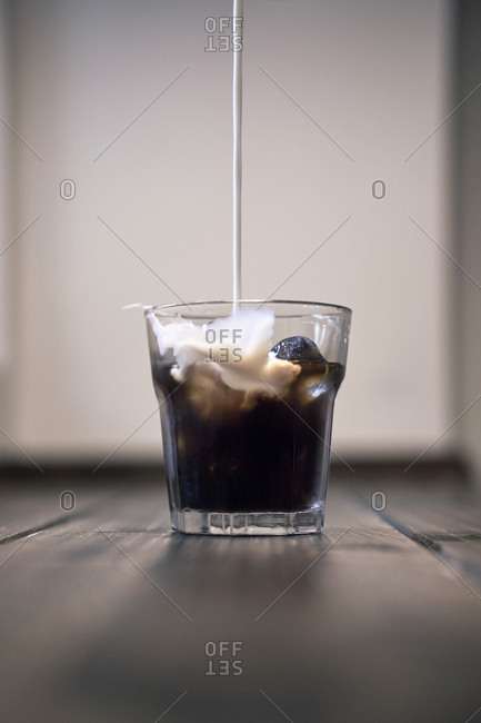 Milk pouring to dark icy coffee in the glass placed on wooden table