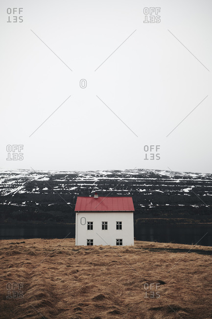 Small house with red roof built at snowy hill in Iceland
