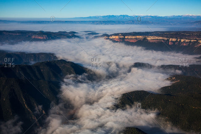 Majestic aerial view of thick clouds floating amidst mountain peaks