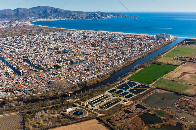 Breathtaking aerial view of green fields and huge coastal city near calm sea