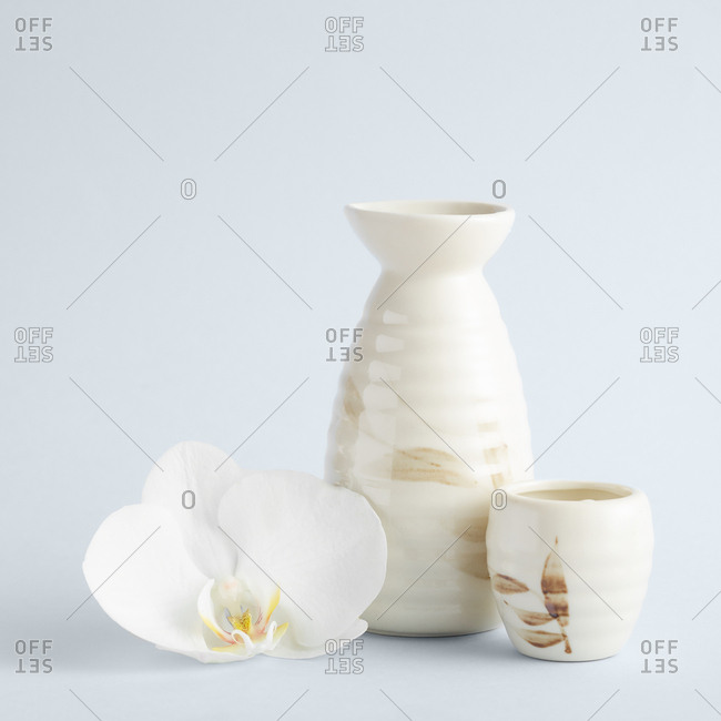 Elegant composition of light ceramic vases with floral ornament standing with white orchid flower nearby on white background
