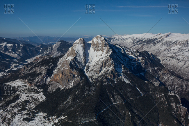 Magnificent aerial view of snowy mountain peak on background of clear sky