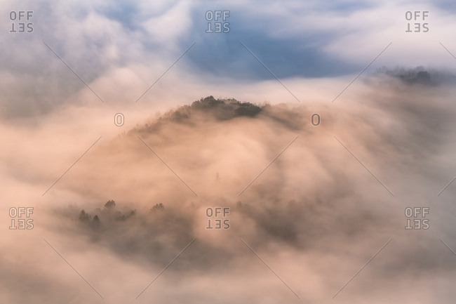 Breathtaking aerial view of thick clouds covering high mountain