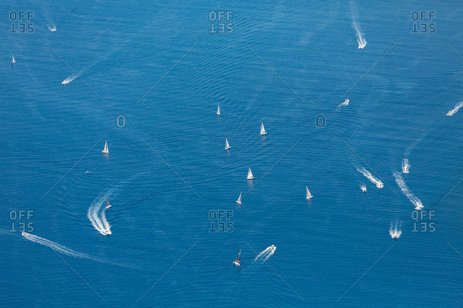 Aerial view of various motorboats floating on surface of calm sea