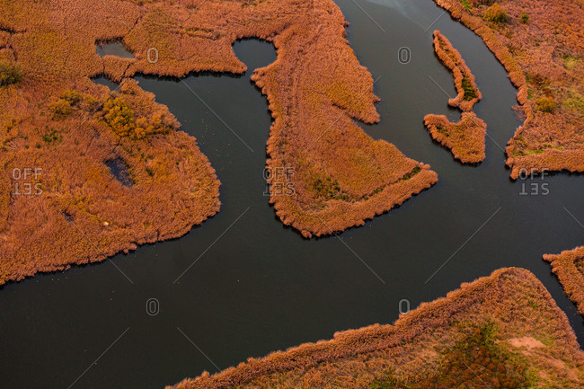 Beautiful aerial view of dark river floating in orange marsh