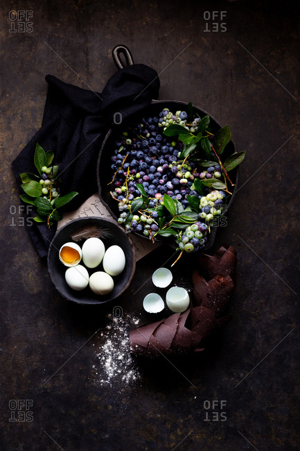 Moody still life of eggs, blueberries, and recipe ingredients
