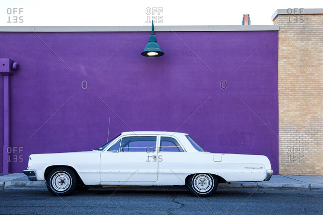 Route 66, New Mexico - June 19, 2018: Restored vintage car in front of colorful wall