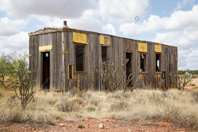 Empty wooden boxcar in desert field
