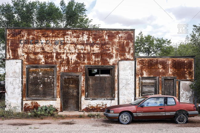 Route 66, New Mexico - June 21, 2018: Rusty abandoned storefront exterior with parked car