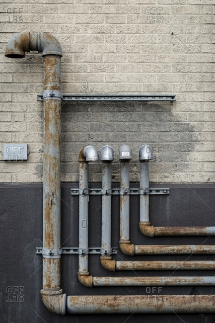 New York City, New York - May 26, 2018: Rusty metal pipes mounted on brick wall