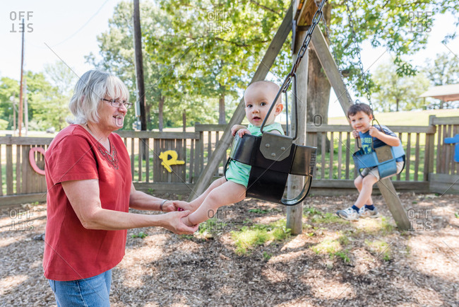 Grandmother pushing baby in swing at park