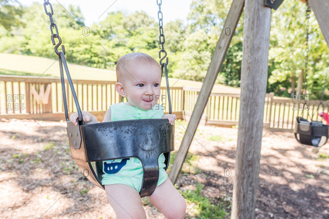 Toddler swinging in park on sunny afternoon