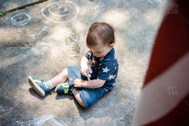 Little boy drawing on arm with chalk alone