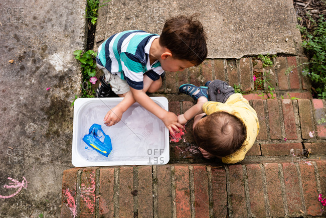 Boys playing with water and chalk on steps